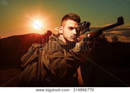 Hunter With Gun And Hunting Form To Hunt In Forest. Calibers Of Hunting Rifles. Hunter With Shotgun