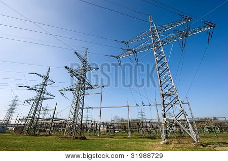 Electricity pylons near an electricity station and blue sky poster