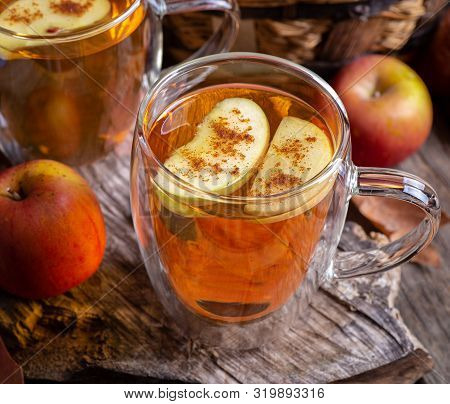 Closeup Of A Glass Mug Of Apple Cider With Apple Slices On A Rustic Wooden Surface