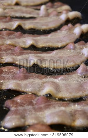 Bacon Sizzling On A Griddle