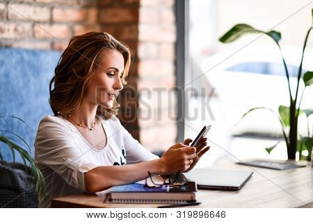 Charming Woman With Beautiful Smile Reading Good News On Mobile Phone During Rest In Coffee Shop, Ha