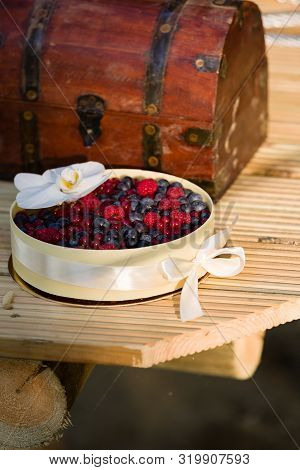 Beautiful Fruit Cake With Flower And Ribbon Bow On Wooden Boards With And Old Fashioned Iron Mounted