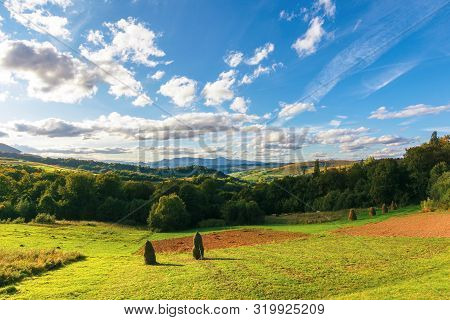 Wonderful Rural Landscape In Evening Light. Hay Stacks On The Field, Forest On Hill. Sky With Clouds