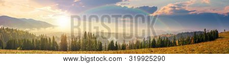 Mountain Panorama With Forest On Meadow At Sunset. Beautiful Autumn Weather. Clouds And Fog Rising A