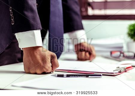 Businessman Strained With Work  Hands In The Office While The Boss Checked His Work.