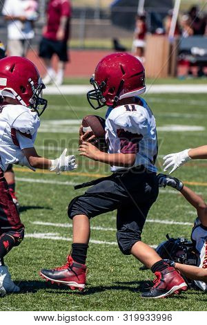Quick and agile youth football player escapes the grasp of gloved defensive hands while running with the ball. poster