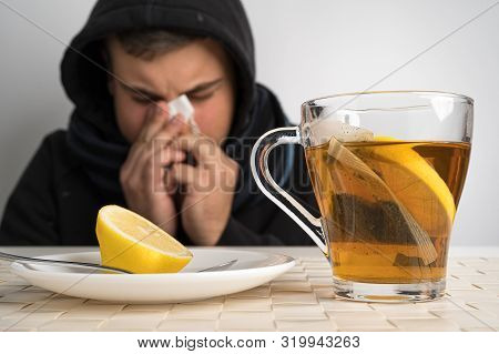 Caucasian Man Blowing Nose Because Of Flu Or Cold. Black Tea With Lemon As A Natural Remedy. Autumn