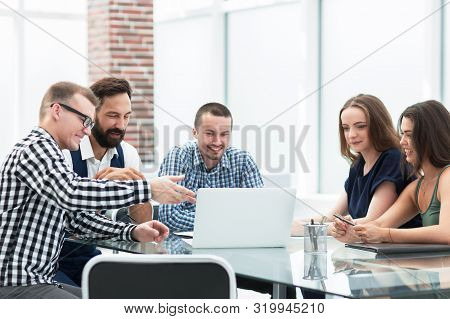 Business Team Looking At The Laptop Screen And Discussing Their Ideas