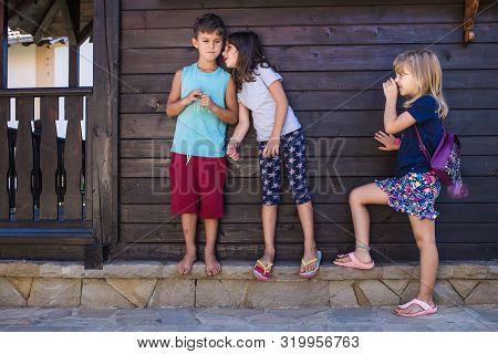 Kids Gossiping. Girl Whispering Something To The Boy, Other Girl Eavesdropping. Kids Playing, Playfu