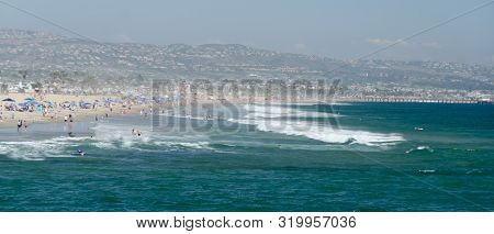 Crowd Of Beachgoers And Strong Surf At Newport Beach With Balboa Pier And Laguna Hils In The Backgro