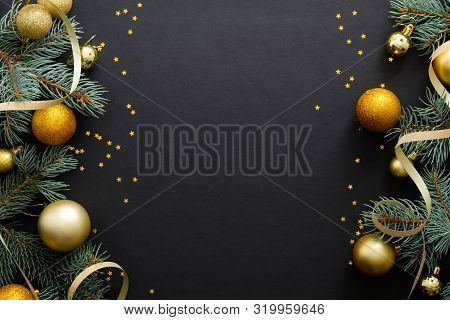 Black Christmas Background With Golden Decorations, Baubles, Fir Tree Branches, Confetti. Christmas