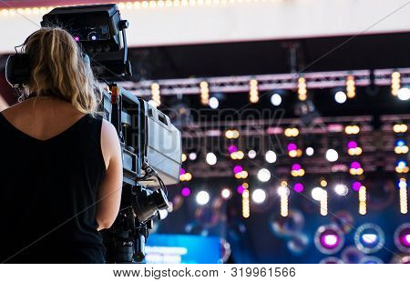 Camerawoman With Professional Video Camera Is Shooting Live Performace.
