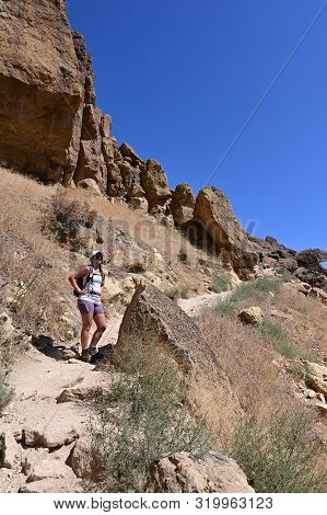 Young Woman On Misery Ridge Trail In Smith Rock State Park Near Terrebonne, Oregon On A Coudless Sum