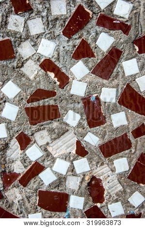 Texture Of A Concrete Wall With Decorative Trimming Pieces Of Bat Tiles - Photo. Facade. Background.