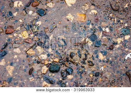 The Texture Of Wet Stones In Shallow Water On The Sand - Photo. Background. River Or Sea Pebbles, Wa
