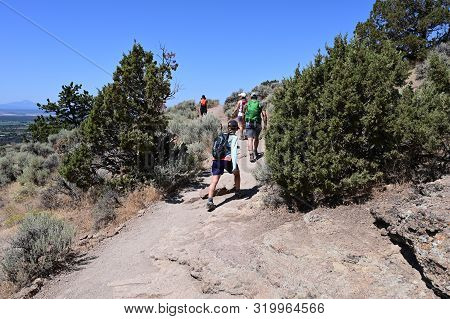 Hikers on Misery Ridge Trail in Smith Rock State Park near Terrebonne, Oregon on a cloudless summer day. poster