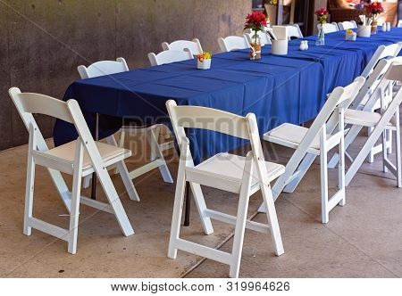 A Long Outdoor Casual Dining Table With Blue Tablecloth And White Chairs Left In Disarray After Gues