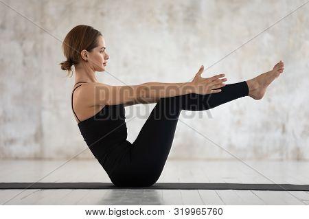 Young Woman Practicing Yoga, Doing Paripurna Navasana Exercise