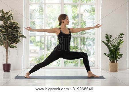 Young Woman Practicing Yoga, Warrior Two Pose, Virabhadrasana Exercise