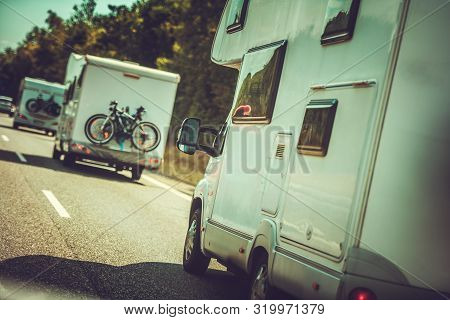 Camper Vans Traffic. Many Rv Recreational Vehicles On The Same Road. Summer Time Vacation In A Motor