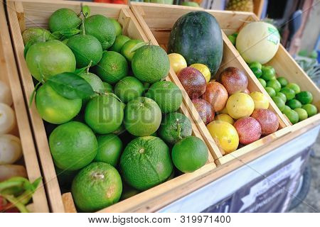 A Lot Of Tangerine And Many Mixed Fruits In A Wooden Hair Basket.