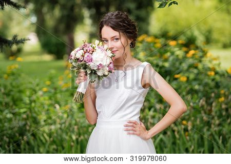 Beautiful Bride In Fashion Wedding Dress On Natural Background. The Stunning Young Bride Is Incredib