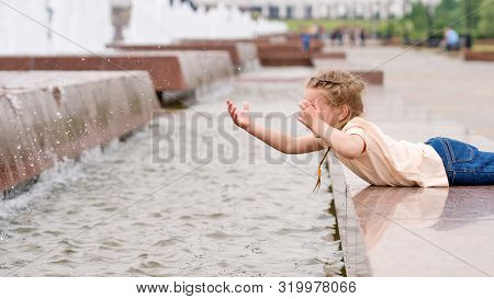 Сute little mischievous girl plays at the fountain. Time of prank. Urban casual outfit. Carefree. Happiness, fun and childhood concept. poster
