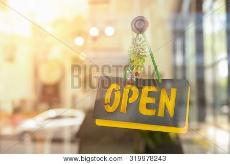 Open Sign Hanging Front Of Cafe With Colorful Bokeh Light Background. Business Service