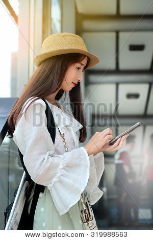 Teen Girl Hold And Chart Text By Using Smart Phone Within Railwal Station.