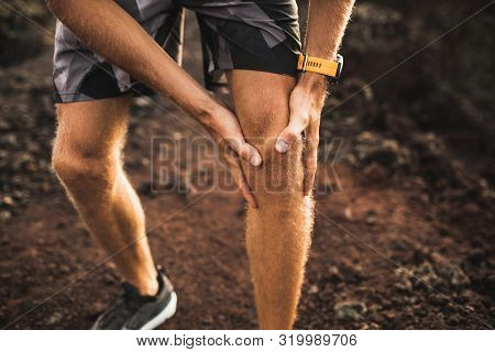 Knee Injury On Running Outdoors. Man Holding Knee By Hands Close-up And Suffering With Pain. Sprain