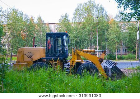 Road Repair Work - An Orange Excavator Stands On The Road Behind A Green Wall Of Grass Against A Bac
