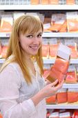 Happy girl wearing white shirt chooses salmon in store; shallow depth of field poster