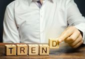 Businessman puts wooden blocks with the word Trend. Popular and relevant topics. New ideological trends. Recent and latest trend. Evaluation methods. poster