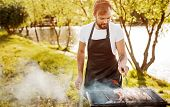Bearded man in apron preparing delicious sausages on hot grill with smoke while cooking for picnic on lake shore poster