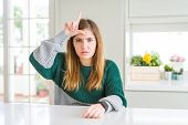 Young beautiful plus size woman wearing casual striped sweater making fun of people with fingers on forehead doing loser gesture mocking and insulting. poster
