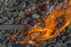 Flames And Hot Coals With Metal Blacksmith Tool