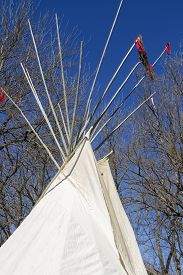 Top Of Traditional Indian Tepee With Poles, Trees, Blue Sky