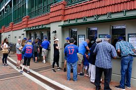 Chicago, IL - August 22, 2019: Fans stand in front of the ticket booth at Wrigley Field before a Chicago Cubs baseball during a beautiful summer day.