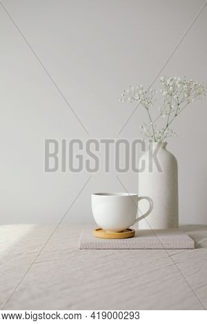 Cup Of Coffee And Vase With Gypsophila Flowers On Table With Linen Tablecloth. White Wall On Backgro