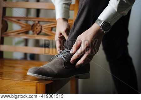 Groom Straightens The Laced Laces With His Foot On The Chair