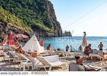 Alanya, Turkey - October 23, 2020: People Sunbathe On Cleopatra Beach At The Foot Of A Cliff In Alan