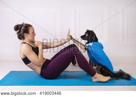 Sport With A Dog. Attractive Girl Working Out On The Blue Fitness Mat With Her Dog. Athletic Woman D