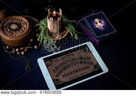 Cartomancy. A Fortune Teller, Tarot Cards. On The Table Are Candles And Fortune-telling Objects. The