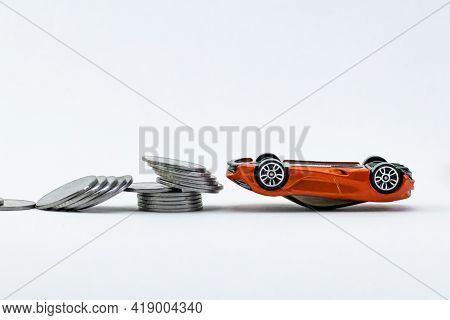 A Toy Car Rolled Upside Down And Scattered Coins In The Side Showing Disaster, Risk Cover Concept