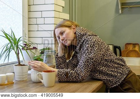 Young Beautiful Woman Dreams Sitting At Home In The Kitchen.