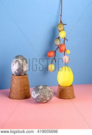 Concept Of Easter. Eggs On A Podium Made Of Peat Pots With A Pink And Blue Background. Abstract East