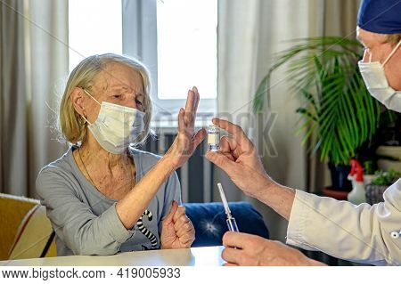 A Caring Doctor Helps A Negative Elderly Grandmother Of 85 Years-a Patient At Home Or In The Hospita