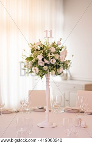 Centerpiece Made Of Green Leaves And Fresh Flowers Stands On The Dinner Table. Wedding Day. Fresh Fl