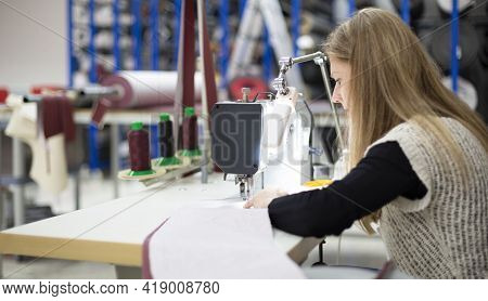 Woman Working Concentrated With An Industrial Sewing Machine. She Is In A Textile Workshop. Selectiv