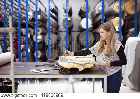 Young Caucasian Woman Working In An Industrial Upholstery Workshop. Space For Text.